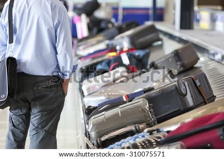 Suitcase on luggage conveyor belt in the baggage claim at airport - stock photo