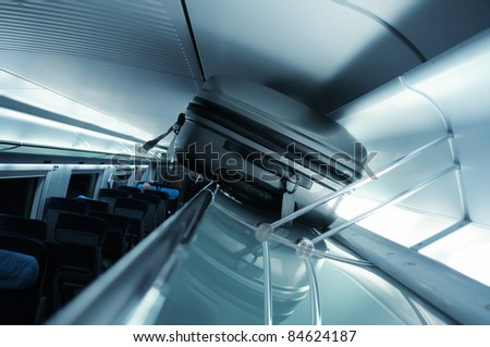 Suitcase on luggage rack in a fast modern train - blue cast business picture - stock photo