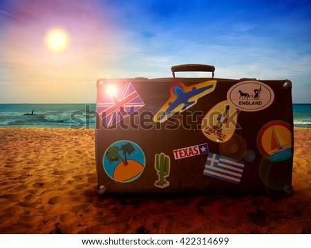 suitcase seasoned traveler on sandy beach at sunset - stock photo