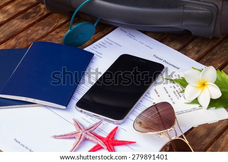 suitcase, travel documents with black smartphone - stock photo