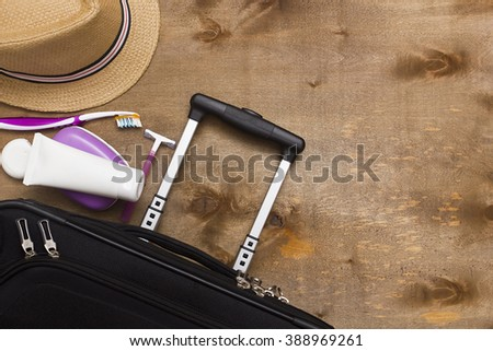 Suitcase traveler, toiletries and a hat on a wooden background. - stock photo