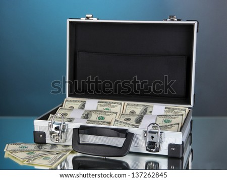 Suitcase with 100 dollar bills on blue background - stock photo