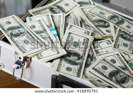 Suitcase with pile of dollars. Opened silver case with money. Better to have bank account. Part of city budget. - stock photo