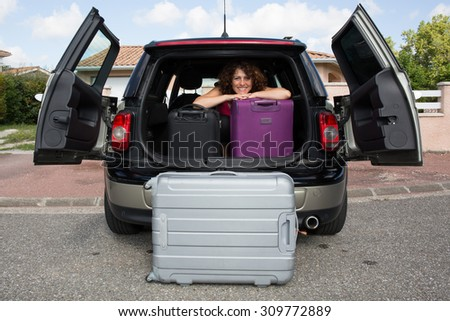 Suitcases and bags in trunk of car and woman ready to go for holidays - stock photo