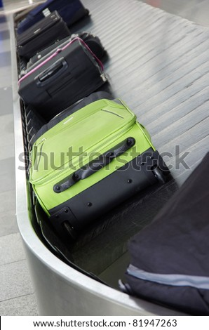 suitcases on the baggage conveyor band on the airport - stock photo