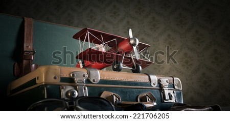 Suitcases on the floor with maps and toy wooden plane. - stock photo