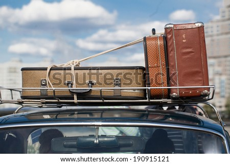 suitcases tied with rope on a car roof - stock photo