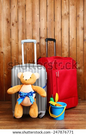 Suitcases with teddy bear and child toys on wooden planks background - stock photo