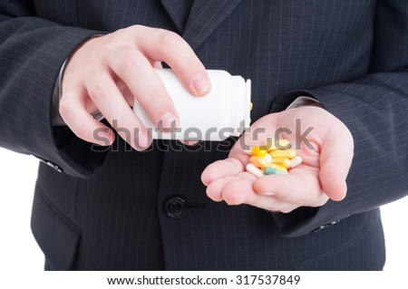Suited doctor hand holding pills from a bottle concept - stock photo