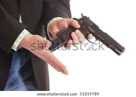 suited guy loading a gun - stock photo