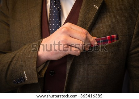 Suited man fixing his pocketsquare - stock photo