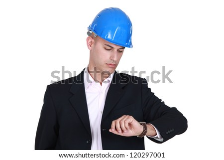 Suited man in a hardhat looking at his watch - stock photo