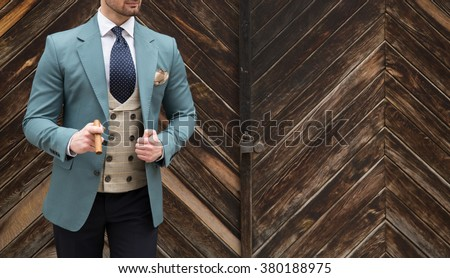 Suited man posing with cigar in his hand - stock photo