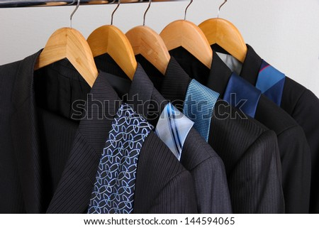 Suits and ties on hangers on gray background