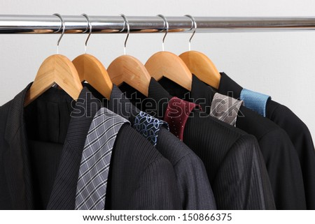 Suits and ties on hangers on gray background - stock photo