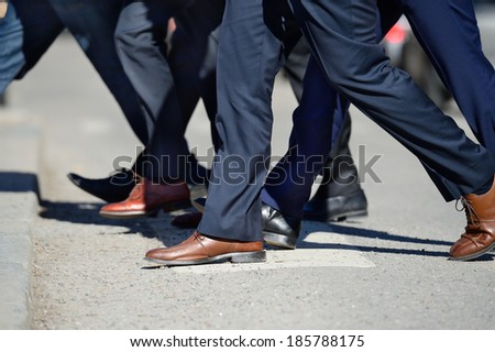 Suits crossing street - stock photo