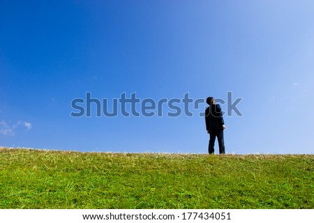 Suits men looking up at the blue sky while standing in grassland