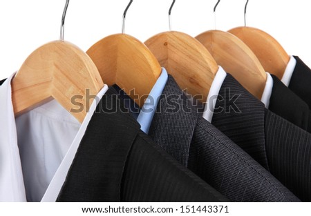 Suits with shirts on hangers on white background
