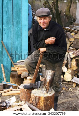 SUKACHI, UKRAINE - NOVEMBER 03 - A man stands next to the deck leaning on an axe in Sukachi on November 03, 2010.