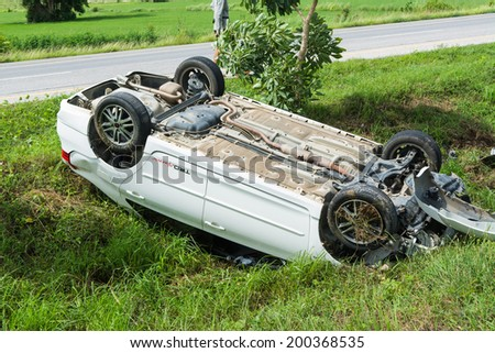 SUKHOTHAI THAILAND-JUNE 22,2014 : car turned upside down at the side of the road because driver is doze off but not be injured. - stock photo