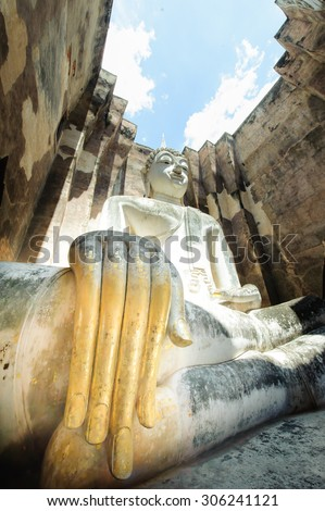 SUKHOTHAI THAILAND: The Main Buddha with golden hand in the temple of Sukhothai historical park in Sukhothai, Thailand  - stock photo