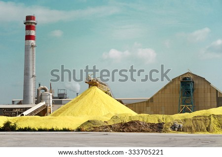Sulfur Factory / A Yellow Pile of Sulfur Produced in an Industrial Facility - stock photo