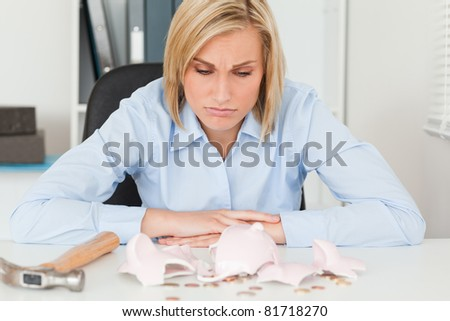 Sulking woman sitting in her office in front of an shattered piggy bank with less in than expected - stock photo