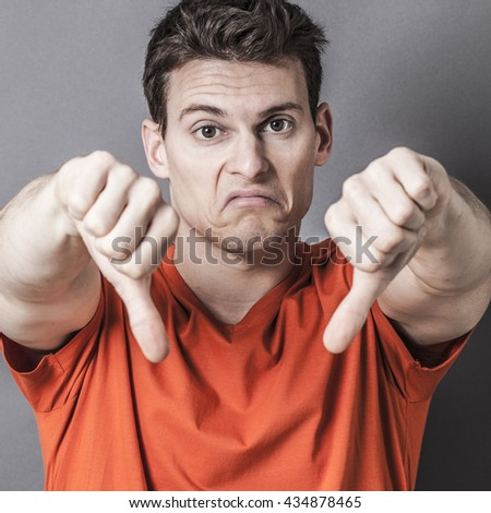 sulking young sporty man showing his dislike and disappointment with thumbs down in the foreground, closeup of his pouting face and loser sign with textured effects  - stock photo