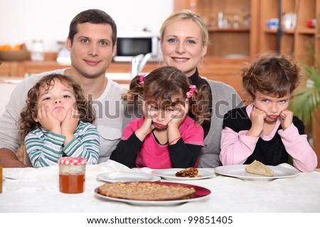 Sulky children with pancakes - stock photo