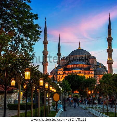 Sultan Ahmed Blue Mosque in Istanbul, Turkey - one of the most popular landmarks in the city. Park, lighted street lamps at night and sunset sky, blurred people - stock photo