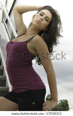Sultry brunette poses on mobile stairs at airport - stock photo