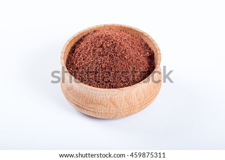 Sumac in a wooden bowl isolated on white background