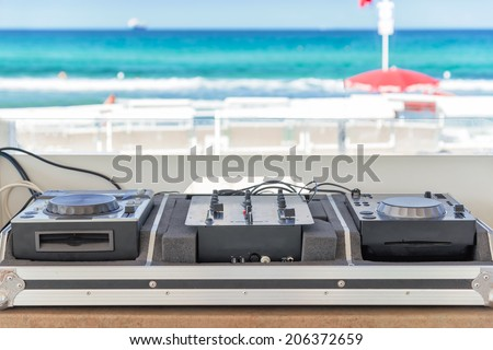 sumer party: dj console on the beach - stock photo