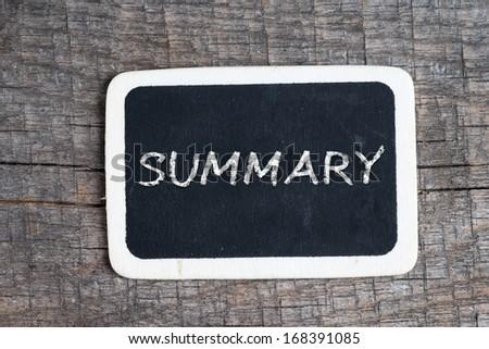 Summary handwritten with white chalk on a blackboard on wood background - stock photo