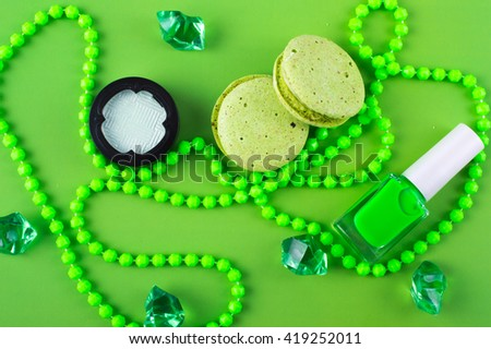 Summer Accessories and Cosmetics for rest on a green background - sunglasses, lipstick, powder, colored beads, nail polish. View from above. Flat lay. - stock photo