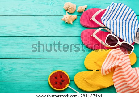 Summer accessories and sweets on blue wooden background - stock photo