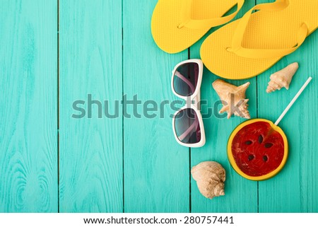 Summer accessories. Sunglasses and flip flops near shells and candy on blue wooden background.  - stock photo