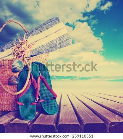 Summer accessories, swimsuit, sun glasses, bag and flip-flops. Closeup of summer beach bag  - stock photo