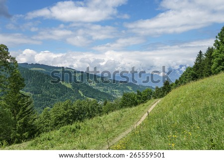 Summer Alpine hiking trail among scenic views - stock photo