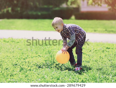 Summer and children concept - little boy having fun playing with ball on the grass  - stock photo