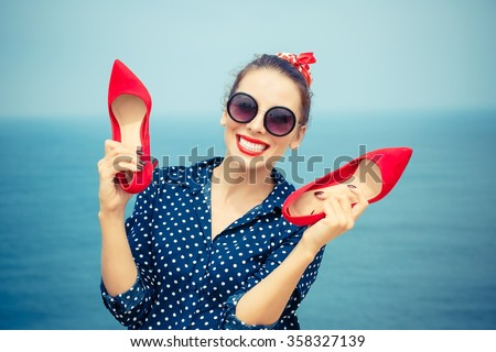 Summer at sea. Closeup portrait beautiful happy free young pretty woman excited stylish fashion girl looking at you camera smiling holding red shoes isolated seascape ocean background outdoor vacation - stock photo
