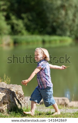 Summer at the lake with a cute little kindergarten aged girl walking purposefully along the edge of the lake shore in her shorts and bare feet