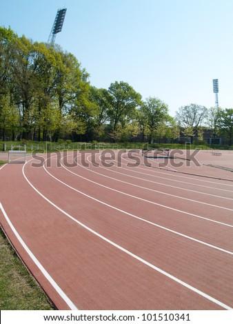 summer athletic stadium with run race tracks and light masts - stock photo