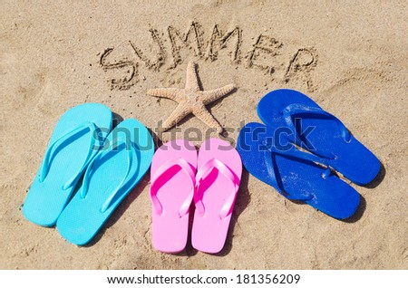 """Summer background with flip flops, starfish and sign """"Summer"""" on the sandy beach - stock photo"""