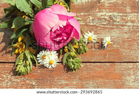 Summer background with wildflowers and peonies on an old table. Space for text. - stock photo