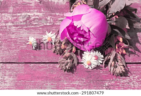 Summer background with wildflowers and peonies on an old table. Space for text. Art processing in lilac shades. - stock photo