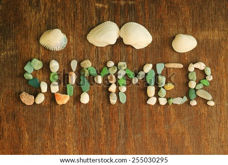 summer background, word summer made of sea shells and stones on wood background - stock photo