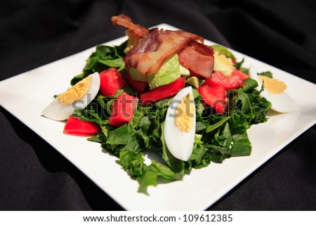 Summer bacon and spinach salad on a white plate, shot with a shallow depth of field - stock photo