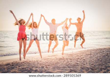 Summer beach at sunset. A group of five friends jumping in the air with his hands to the sky on the beach. Three women and two men jumping with sun at sunset behind them