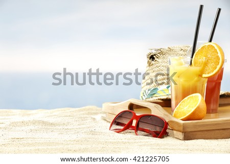 summer beach background of sand wooden brown tray and few drinks and hat